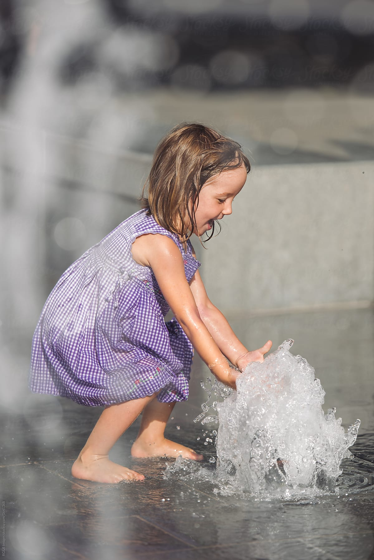 Portrait Of Wet Little Girl Playing At The Fountain