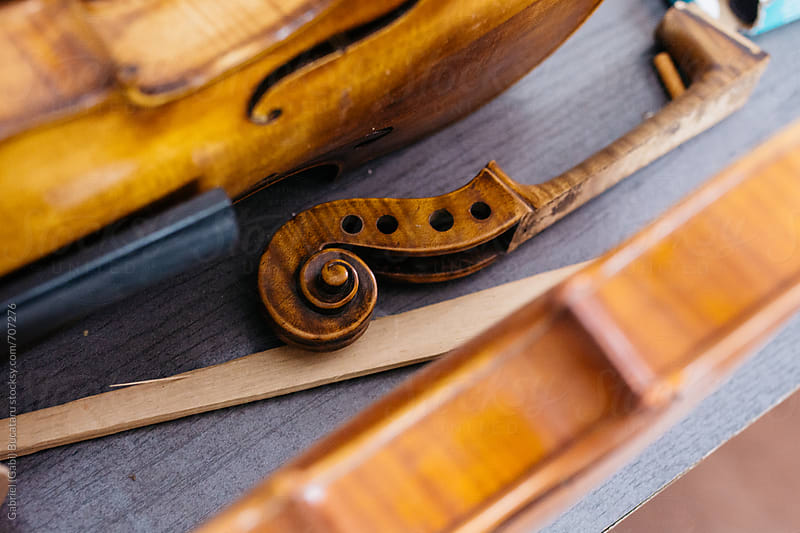 Violin body and a scroll on a workbench by Gabriel (Gabi) Bucataru for Stocksy United