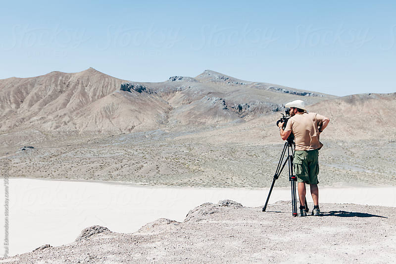 Man looking through digital cinema camera, expansive desert in distance by Paul Edmondson for Stocksy United