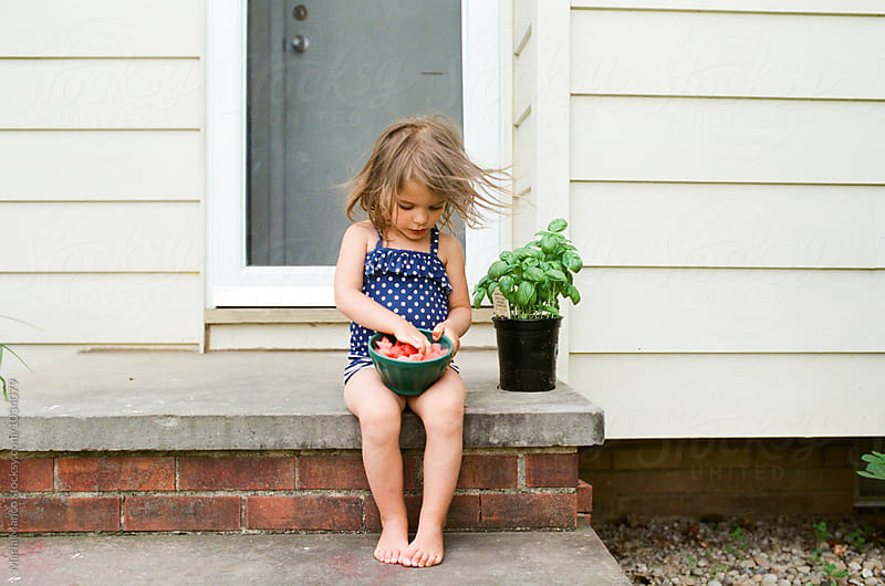 little girl eating watermelon by Maria Manco for Stocksy United