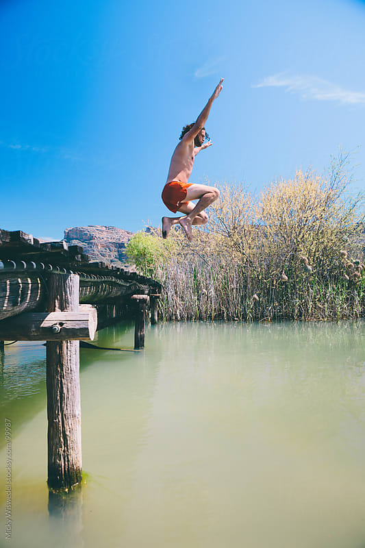 Man jumping off a bridge into a river by Micky Wiswedel for Stocksy United