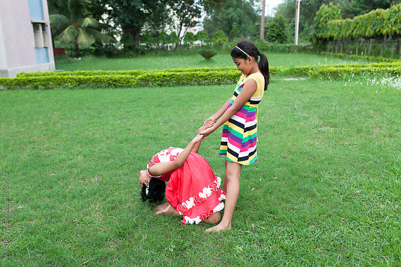 teenage girl helping other girl to perform Yoga by PARTHA PAL for Stocksy United
