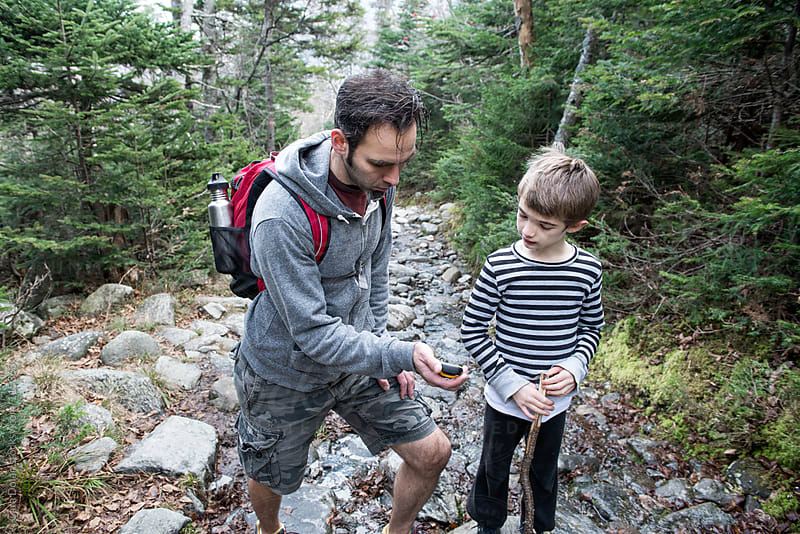 Father and son hiking on in the mountains use a hand-held GPS to track their progress by Cara Dolan for Stocksy United