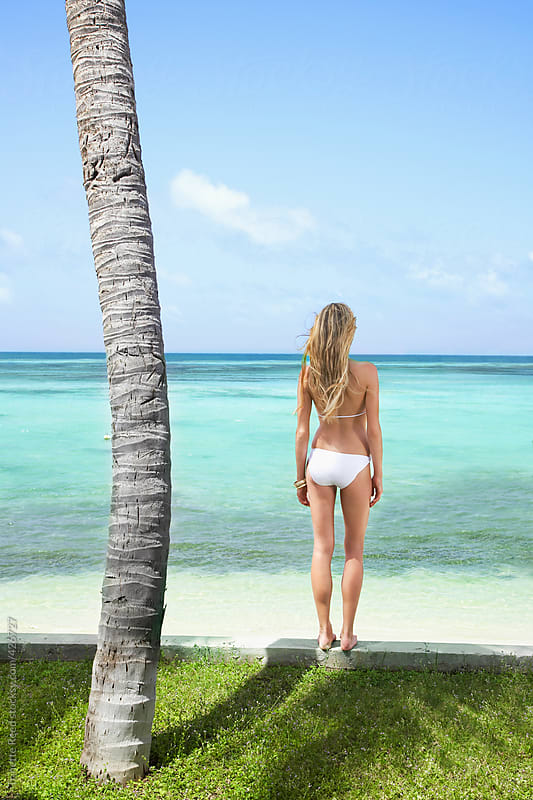 Beautiful woman relaxing on beach at luxury resort by Trinette Reed for Stocksy United