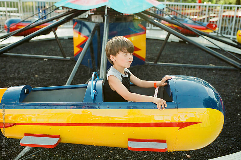 child on ride at amusement park by Maria Manco for Stocksy United