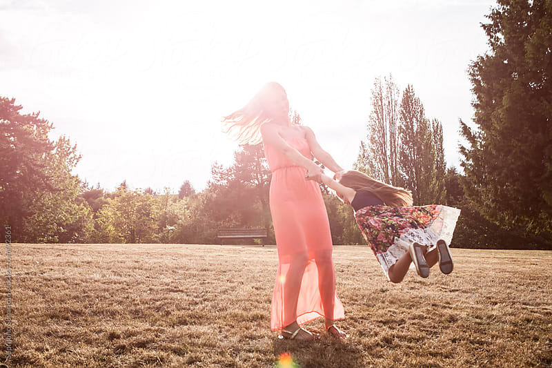 Mother swinging her daughter in a park by Suprijono Suharjoto for Stocksy United
