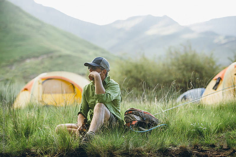 hiker fly fisherman relaxing at a camp in the mountains by Micky Wiswedel for Stocksy United