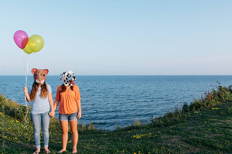 Two teenage girls with squirrel and dog masks by a sea shore holding balloons by Gabriel (Gabi) Bucataru for Stocksy United