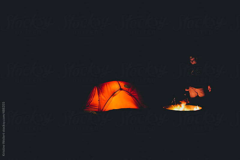 Man camping at night with his tent and fire by Kristine Weilert for Stocksy United