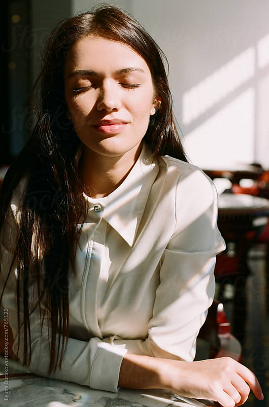 Woman enjoys the sun in a cafe by Lyuba Burakova for Stocksy United