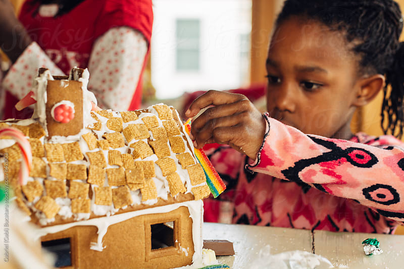 Young black girl working on a gingerbread house by Gabriel (Gabi) Bucataru for Stocksy United