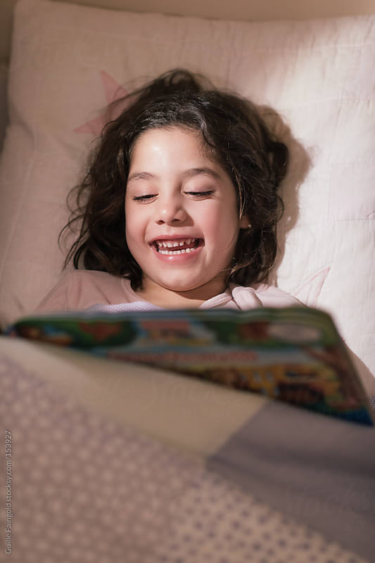 Laughing girl with book in bed. by Guille Faingold for Stocksy United