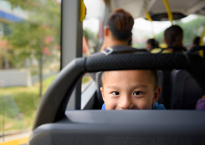 Child looking at camera on bus by Lawren Lu for Stocksy United