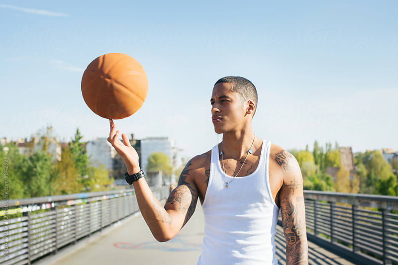 Outdoor Portrait of Young Mixed Race Man Spinning Basketball on One Finger by Julien L. Balmer for Stocksy United