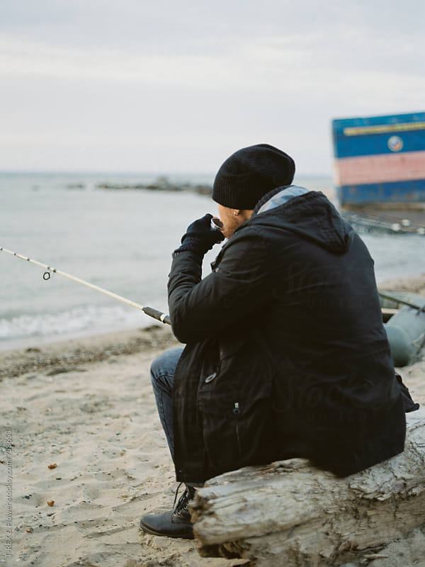 Man fishing while sittting on sandy shore. by Danil Nevsky for Stocksy United