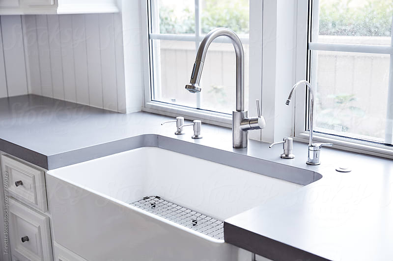 White Farmhouse sink with concrete countertops by Trinette Reed for Stocksy United