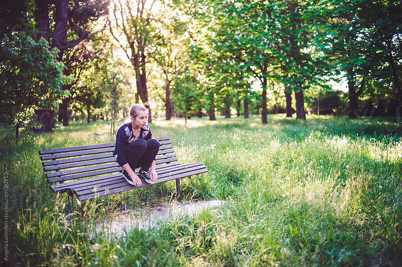Girl sitting on a bench in a park by Angela Lumsden for Stocksy United