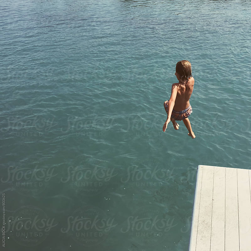 A Boy Jumping Into A Lake On A Hot Summer Day by ALICIA BOCK for Stocksy United