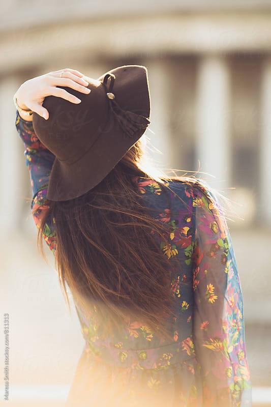 Brunette model holding onto her floppy hat, looking up by Maresa Smith for Stocksy United