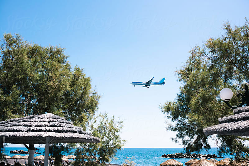 Plane is landing above a beach in Santorini by GIC for Stocksy United