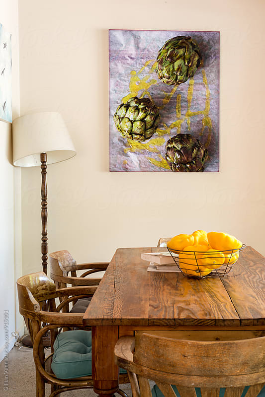 interior of a cafe with table, lamp and artwork by Gillian Vann for Stocksy United