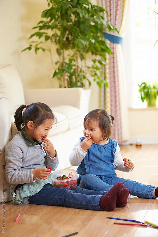 two little asian girls eating strawberry indoor by Bo Bo for Stocksy United