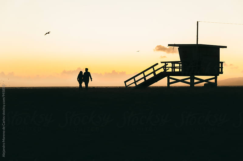 Silhouette of lifeguard cabin and couple holding hands at sunset by Alejandro Moreno de Carlos for Stocksy United