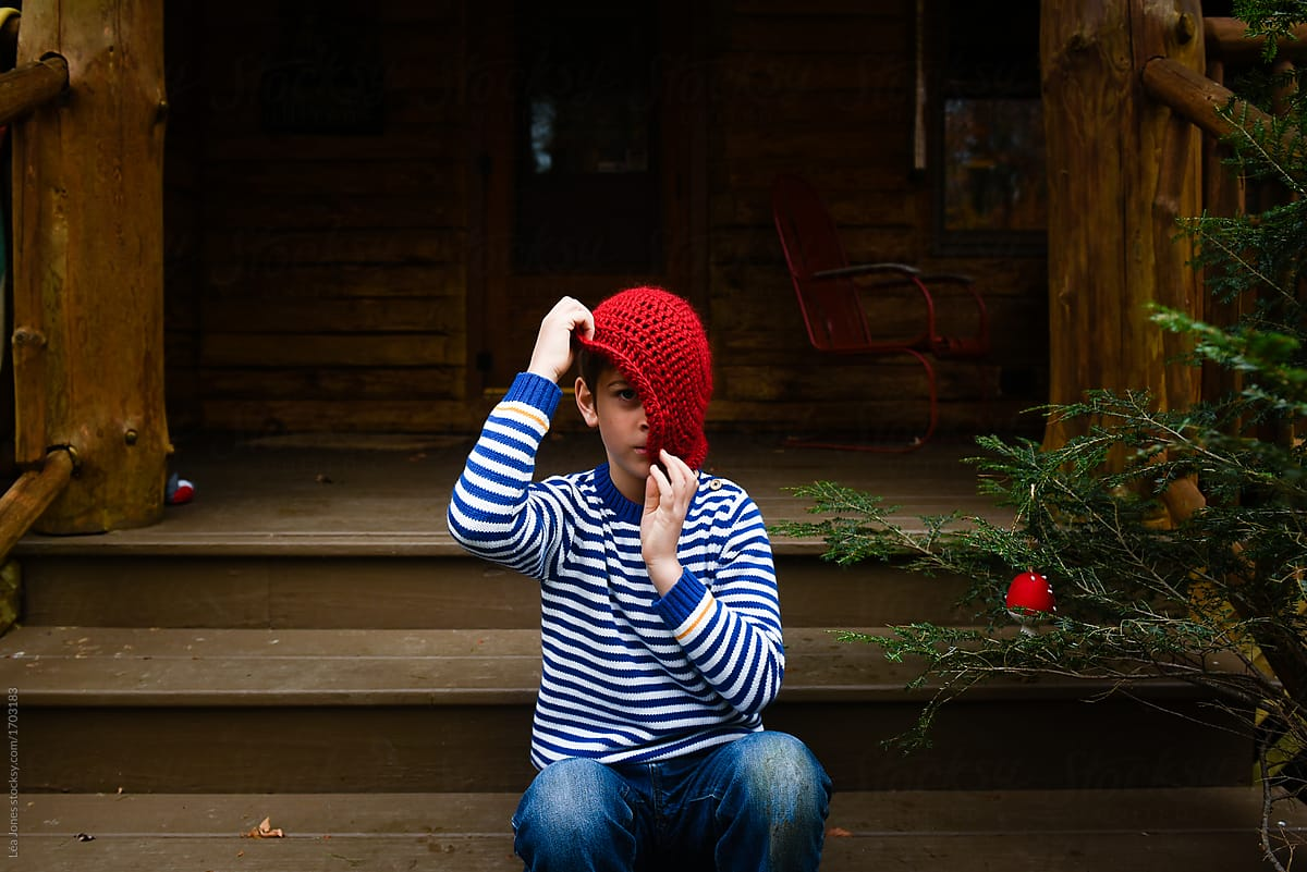 little boy taking a silly pose with a red wooly hat by Léa Jones for Stocksy eb12473be7a