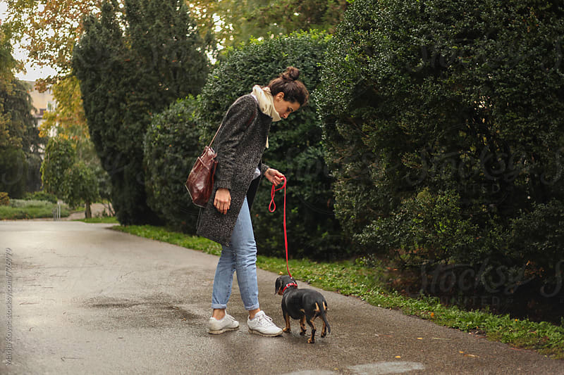 Brunette in a park walking with her black dog by Marija Kovac for Stocksy United