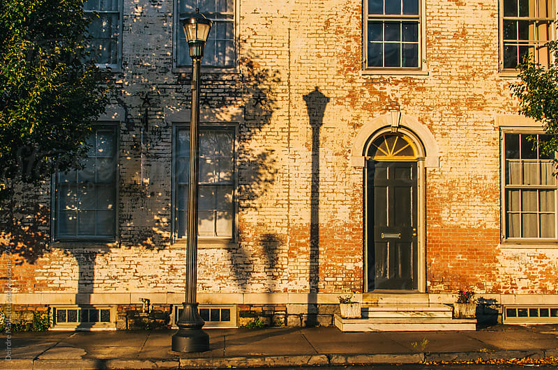 old brick building with shadows at sunset by Deirdre Malfatto for Stocksy United