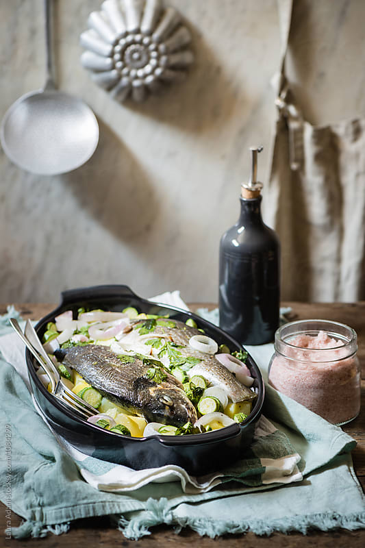 Seabream with potato, cougettes and onions in a fish steamer by Laura Adani for Stocksy United