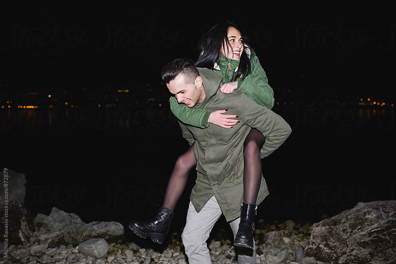 Happy teenage couple having fun together at night by michela ravasio for Stocksy United