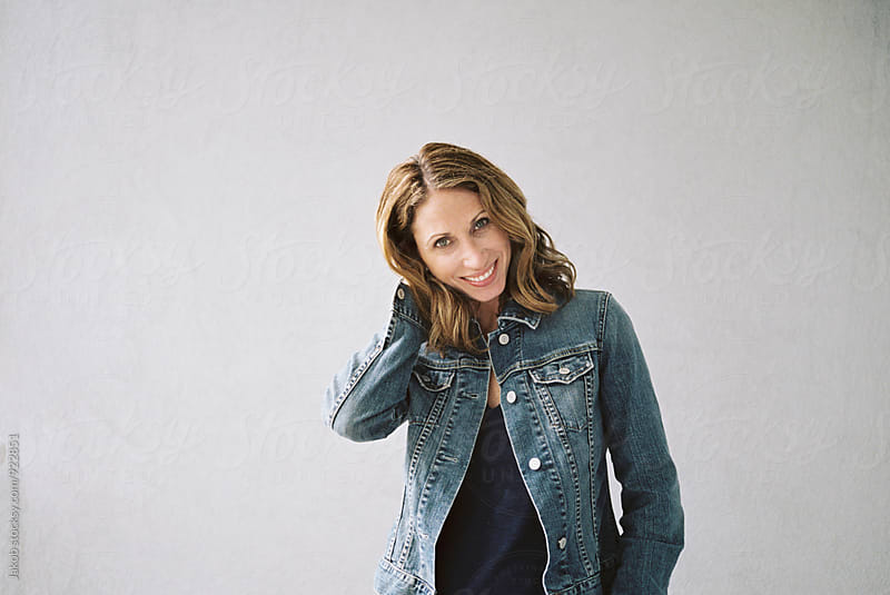 Portrait of a smiling attractive woman in a  denim jacket by Jakob for Stocksy United