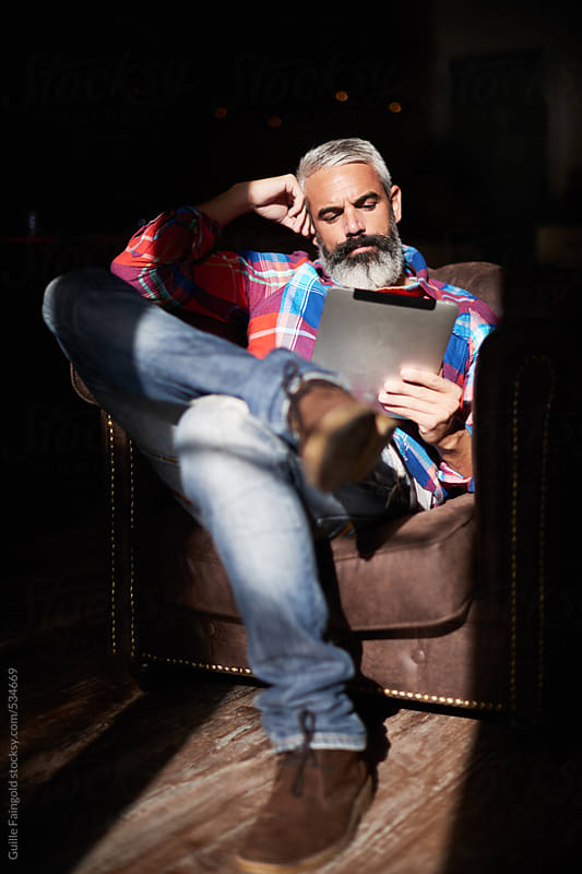 Handsome bearded man using his tablet  by Guille Faingold for Stocksy United