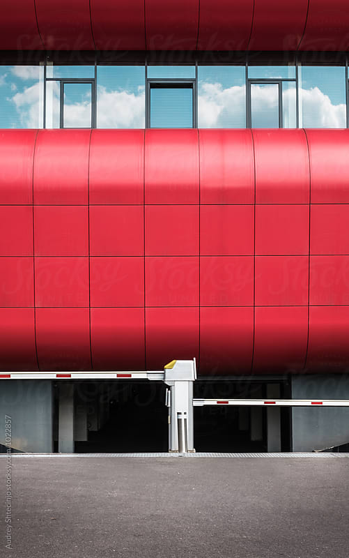 Red modern building with garage entrance  in front of it by Audrey Shtecinjo for Stocksy United