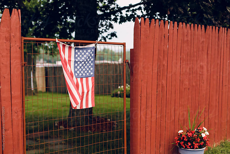 An Amerian flag hangs on an old gate between a red fence. by Holly Clark for Stocksy United