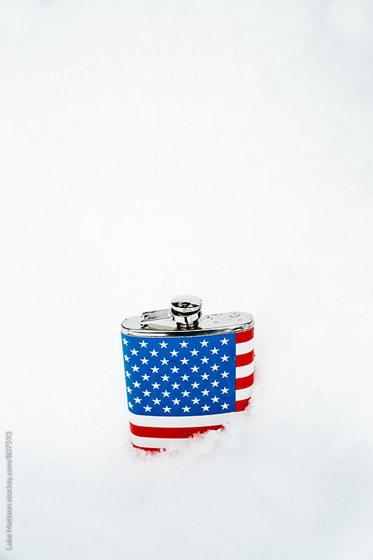 American Flag Flask Half Buried In Deep Snow by Luke Mattson for Stocksy United