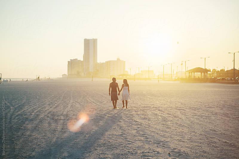 Couple walking on beach holding hands by Borislav Zhuykov for Stocksy United