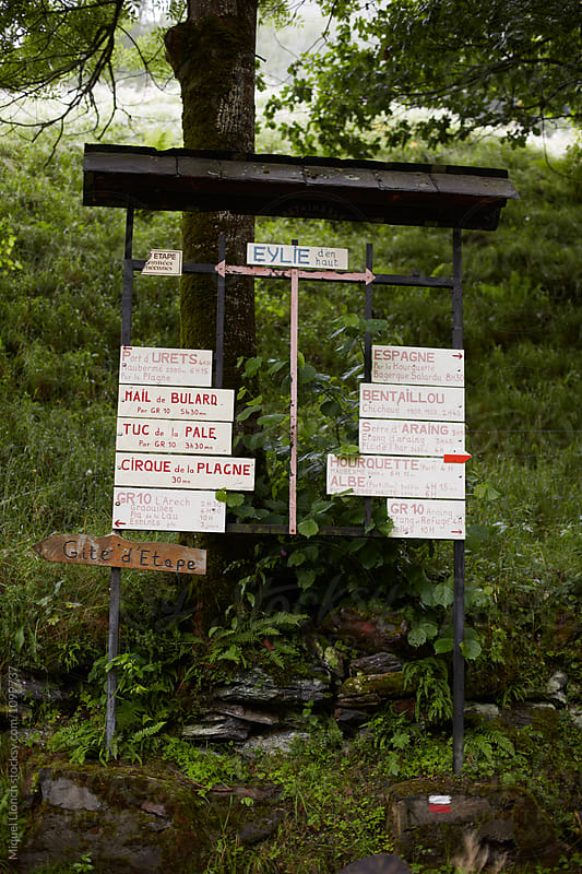 Multiple sign post for marked trails and schedules by Miquel Llonch for Stocksy United