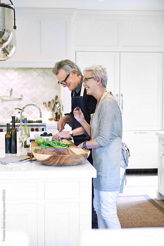 Mature couple with grey hair cooking in kitchen of luxury home by Trinette Reed for Stocksy United