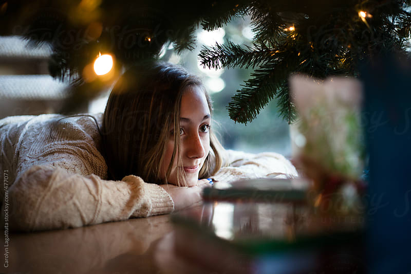 Teenage girl looking at the Christmas presents under the tree by Carolyn Lagattuta for Stocksy United