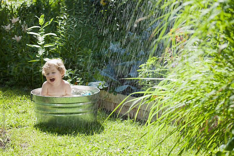 Toddler playing in an aluminum tub outside in the garden  by Edward Bock for Stocksy United