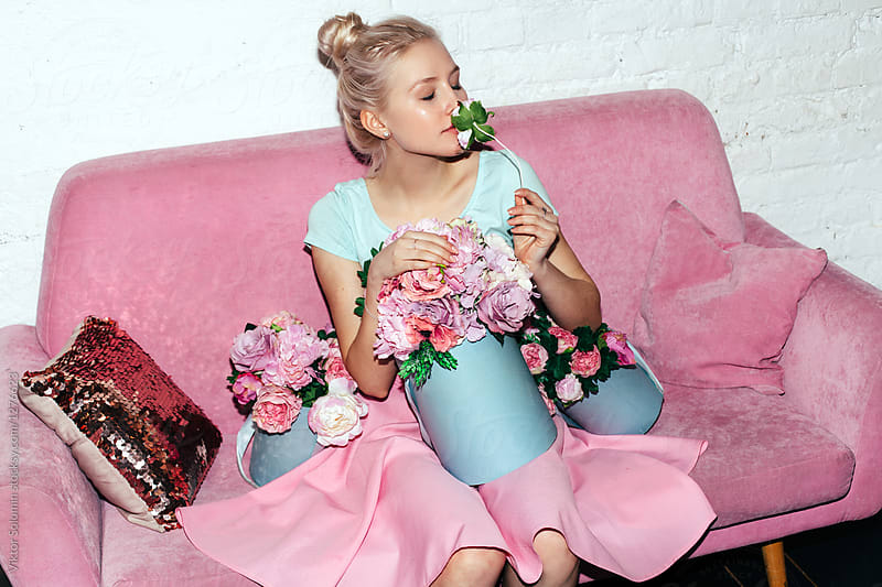 Beautiful blonde fashion woman posing on pink sofa with pink flowers dressed in pink skirt