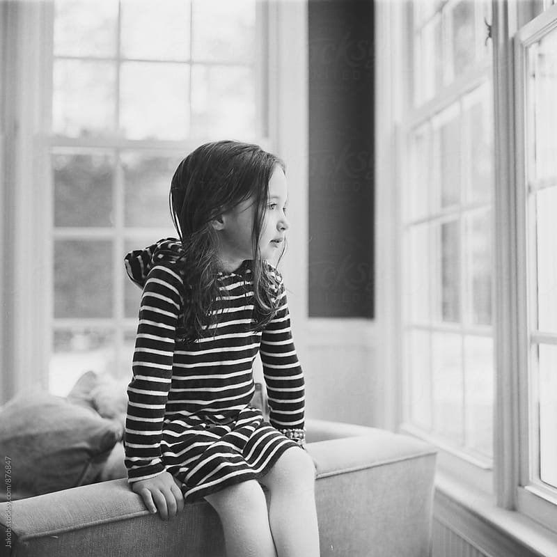 Cute young girl sitting in a chair looking out a window by Jakob for Stocksy United