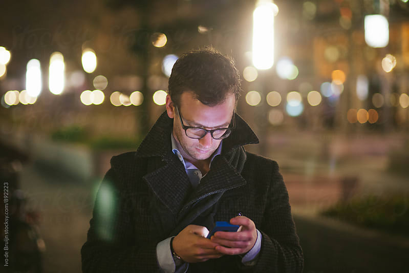 Young business man looking at his phone in the evening by Ivo de Bruijn for Stocksy United