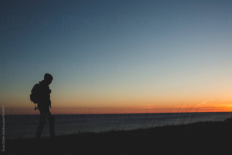 Hiker On Cliff At Sunset by Evan Dalen for Stocksy United