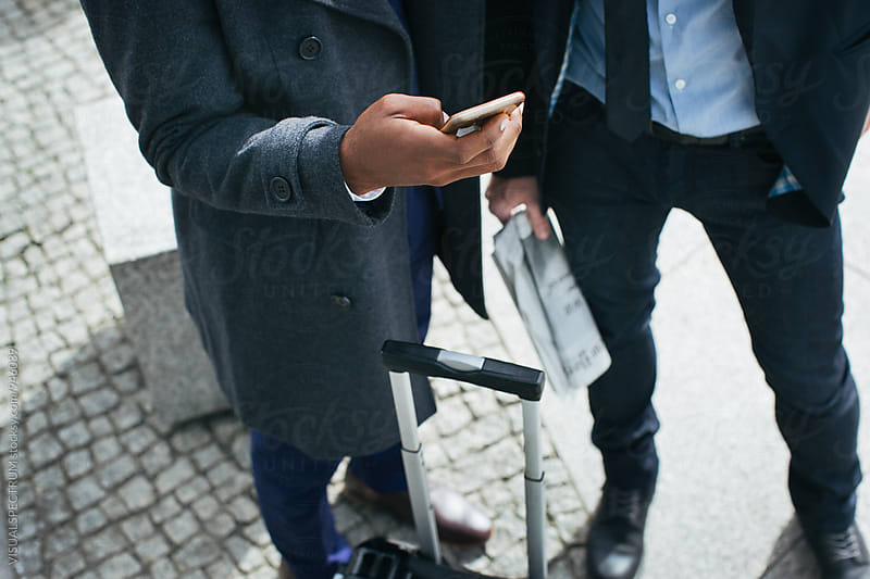 Closeup of Two Businessmen Looking at Cellphone by Julien L. Balmer for Stocksy United
