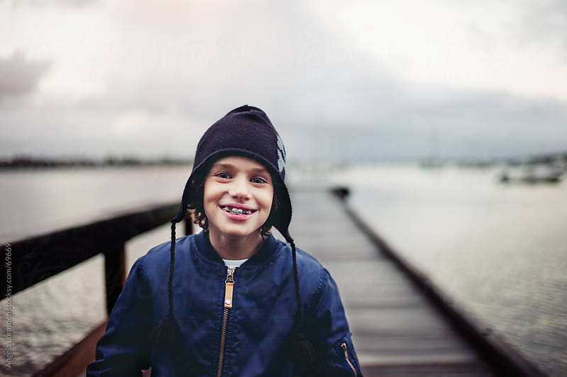 Young boy with a big smile standing on a dock  by Angela Lumsden for Stocksy United