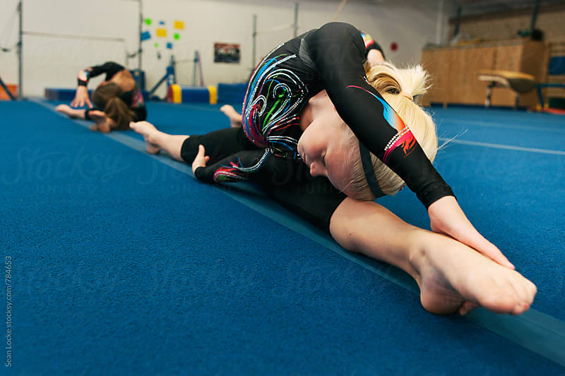 Gymnastics: Team Of Gymnasts Stretch Out Before Practice by Sean Locke for Stocksy United