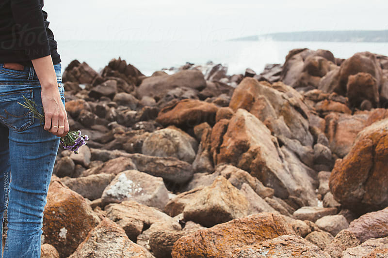 Close up of a woman's leg as she stands on rocks overlooking the ocean by Jacqui Miller for Stocksy United